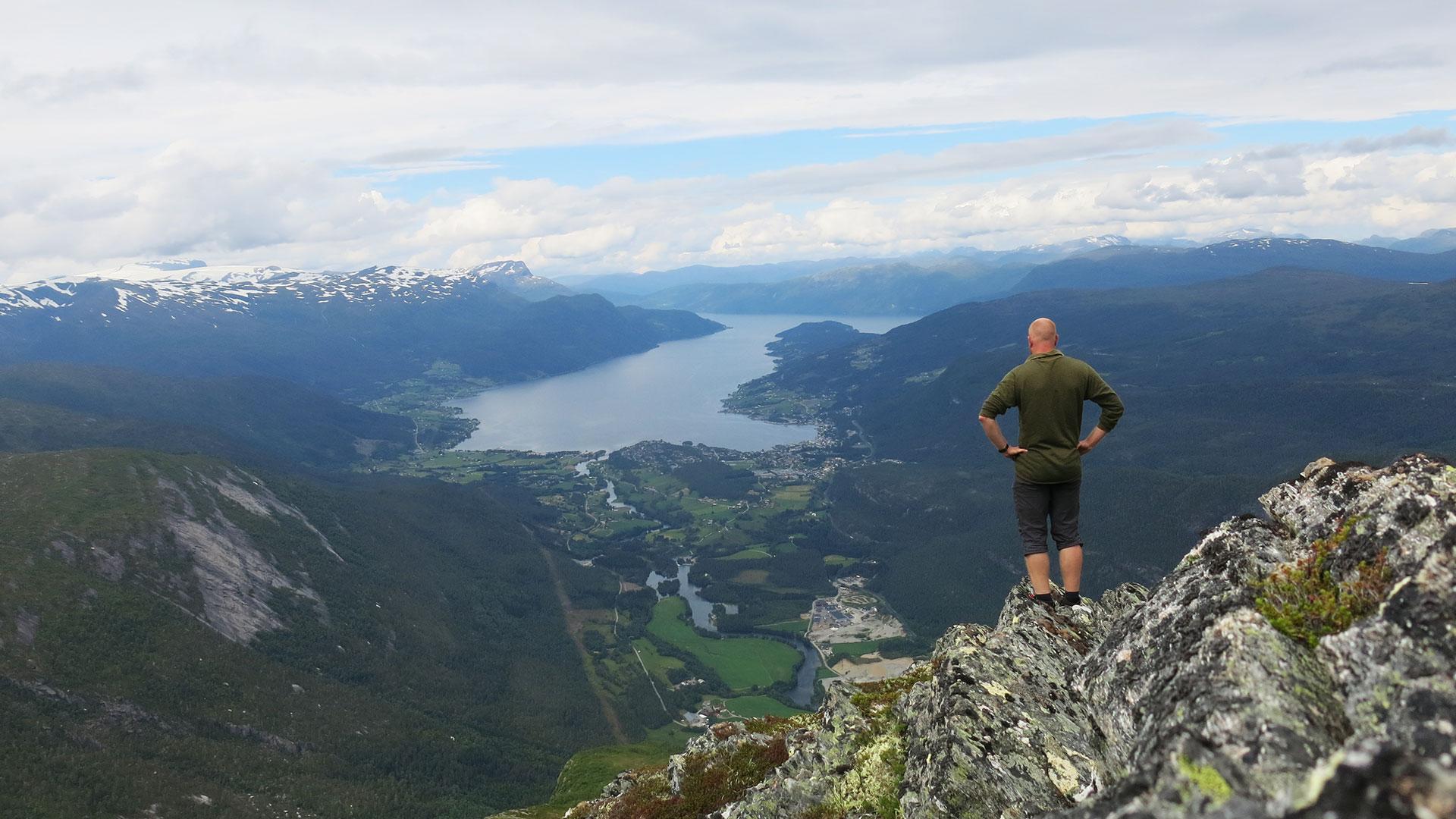 Mann ser utover landskap og fjorden